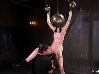 Bald bitch with hands and head in metal balls