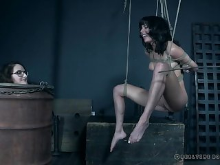 Pretty girl in a rope bondage suspension gets her pussy vibrated