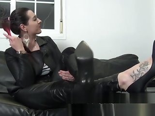 Femdom Mistress In Full Leather Outfit Puts On Long Gloves